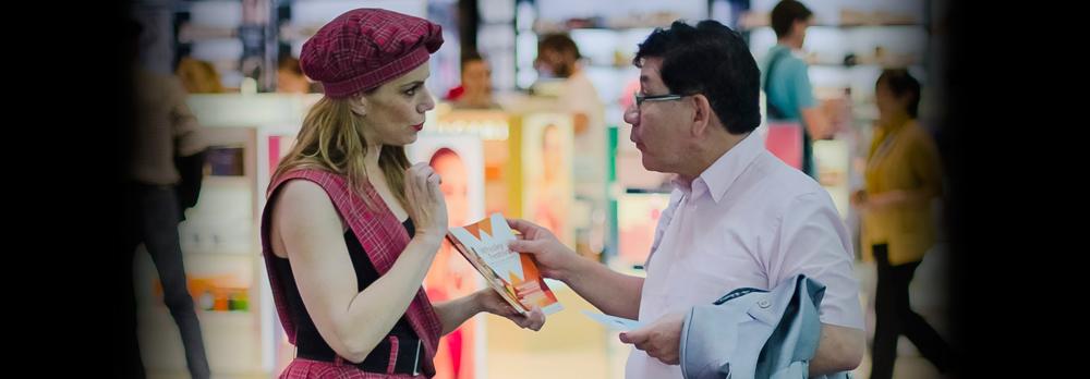 Azafata bailarina de Mat-Woman entrega voucher promocional a cliente.